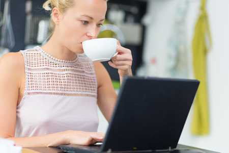 Business woman working remotly from her dining table while having her morning coffee  Home kitchen in the background  photo