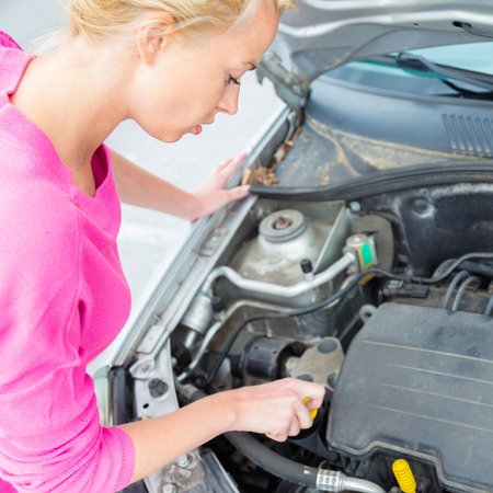 self sufficient: Self-sufficient confident modern young woman checking level of the engine oil in the car  Stock Photo