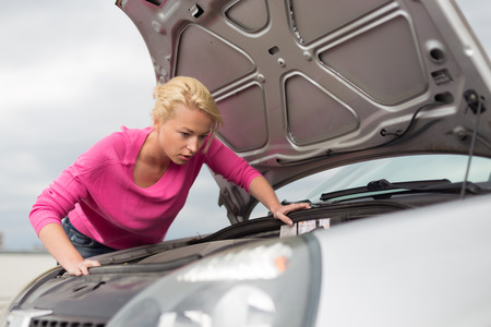 car trouble: Self-sufficient confident modern young woman inspecting broken car engine  Stock Photo