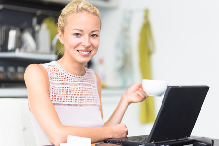 Happy business woman working from her home having more time for her family and her morning coffee  photo