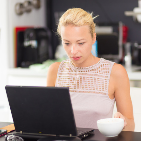 conference room table: Business woman working remotly from her dining table  Home kitchen in the background