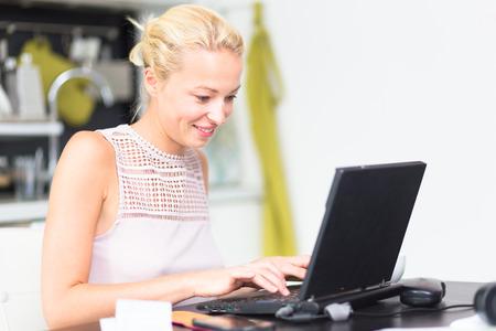 mecanograf�a: Mujer de negocios que trabaja remotly de su mesa de comedor Cocina de una casa en el fondo