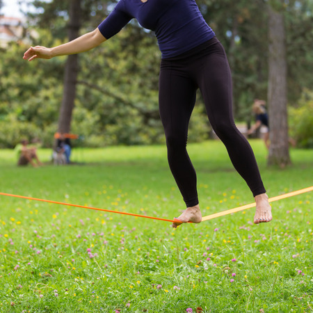 Lady practising slack line in the city park. Slacklining is a practice in balance that typically uses nylon or polyester webbing tensioned between two anchor points. photo