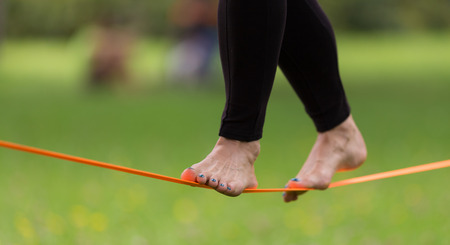 Lady practising slack line in the city park. Slacklining is a practice in balance that typically uses nylon or polyester webbing tensioned between two anchor points. Stock Photo