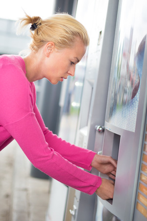Pretty young girl wearing pink top collecting product from an automatic vending machine .  photo