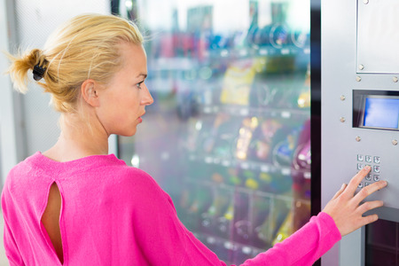 dispenser: Caucasian woman wearing pink top using a coin operated modern vending machine. Her hand is placed on the dial pad and she is looking on the small display screen. Stock Photo
