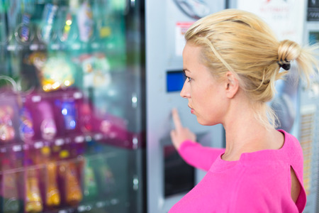 Caucasian woman wearing pink using a modern vending machine. Her right hand is placed on the dia pad. Stock Photo