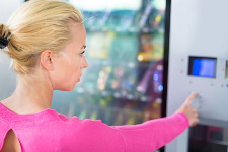vending: Caucasian woman using a vending machine that dispenses snacks. She is looking on the blue display screen of machine.