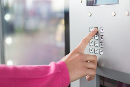 vending: Womens hand using a dial pad on a machine. The fore finger is placed on the dial pad key and is about to press on that. Small sized display with blue light is also visible.