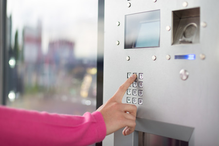 Lady\'s hand using a dial pad on a vending machine. The fore finger is placed on the dial pad key.