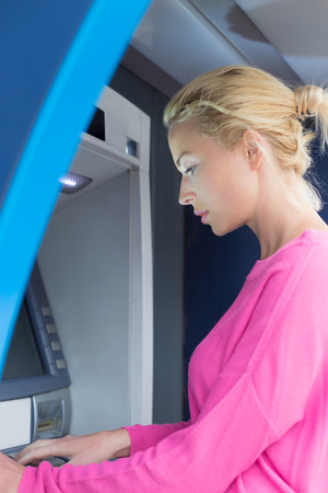 Blonde lady using an automated teller machine . Woman withdrawing money or checking account balance.