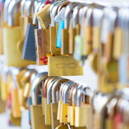 symbolize: Lockers at the bridge symbolize love for ever. Lovers lock the locker on fance and throw key in river to be lost forever. Stock Photo