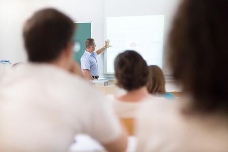 curso de capacitacion: Profesor en la universidad frente a una pantalla de la pizarra. Estudiantes escuchando a dar una conferencia y tomar notas.