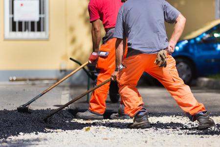 Travailleurs de la construction au cours de bitumage des travaux routiers portant des combinaisons. Le travail manuel sur le site de construction. Banque d'images - 31204807