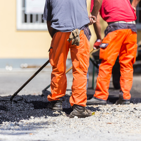 road works: Construction workers during asphalting road works wearing coveralls. Manual labor on construction site.