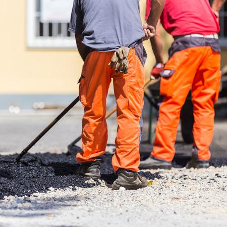 mantenimiento: Trabajadores de la construcción durante el asfaltado de carreteras que llevan overoles. El trabajo manual en el sitio de construcción. Foto de archivo