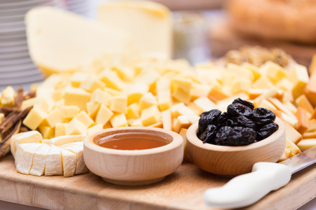 sliced cheese: Cheese Plate with Dried Fruit and Honey. Rustic decoration on a wooden plate.