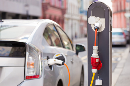 Close-up van de voeding aangesloten op een elektrische auto wordt opgeladen.