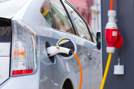 hybrid car: Close up of the power supply plugged into an electric car being charged.