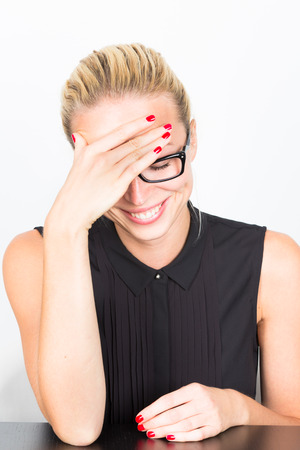 embarrassed: Relaxed cheerful business woman wearing black glasses blushing of embarrassment. Stock Photo