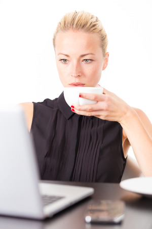 Business woman holding white cup of coffee in her hand while checking some information on her laptop computer in office photo