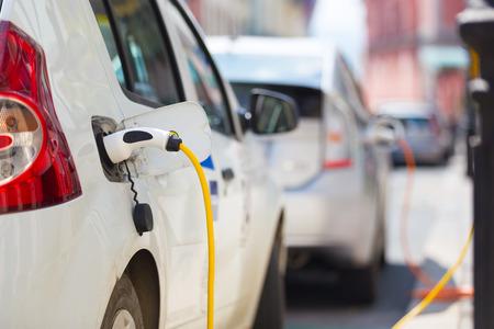 bateria: Fuente de alimentación para la carga del coche eléctrico. Estación eléctrica de carga del coche. Cerca de la fuente de alimentación enchufado en un coche eléctrico está cargando.