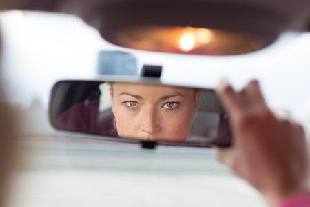 espejo: Hermosa dama joven mirando hacia atrás a través del espejo retrovisor desde el asiento delantero de un automóvil durante la marcha atrás. Foto de archivo