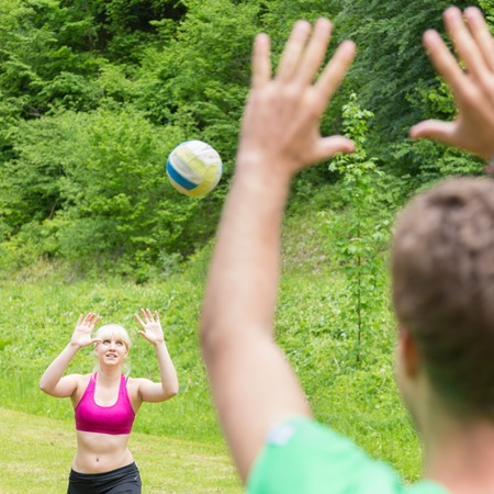Young sporty couple playing volleyball outdoors in park.\ Healthy active lifestyle. Activities in nature.