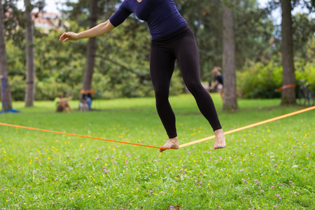 slack: Lady practising slack line in the city park. Slacklining is a practice in balance that typically uses nylon or polyester webbing tensioned between two anchor points. Stock Photo