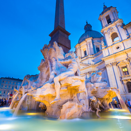 navona: Fountain of the four Rivers and SantAgnese in Agone on Navona square in Rome, Italy, Europe shot at dusk.