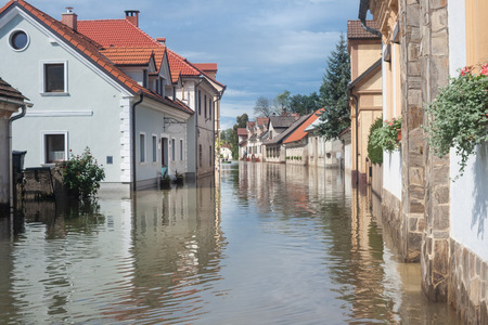 Rural village houses in floodwater. Road with the river overflown with the residents in their homes. Floods and flooding the streets. Natural disaster.