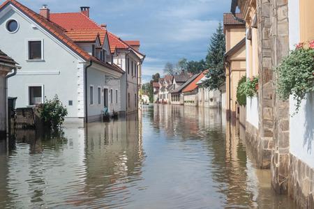 Casas de pueblo rural de agua de la inundación. Camino con el río desbordado con los residentes en sus hogares. Las inundaciones y las inundaciones de las calles. Desastre natural.