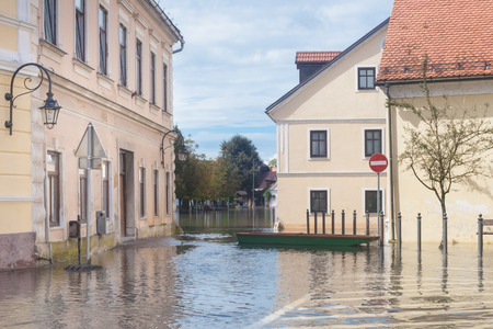 FLOODING: Rural village houses in floodwater. Road with the river overflown with the residents in their homes. Floods and flooding the streets. Natural disaster.