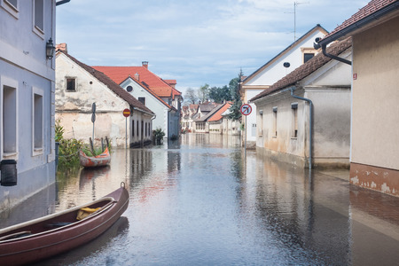 Rural village houses in floodwater. Road with the river overflown with the residents in their homes. Floods and flooding the streets. Natural disaster.   photo