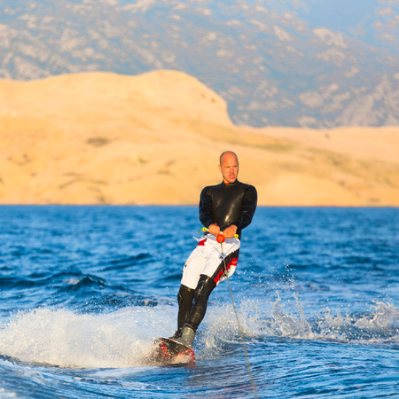 involves: Wakeboarder in wetsuit riding in sunset. Wakeboarding is a surface water sport which involves riding a wakeboard over the surface of a body of water. Stock Photo