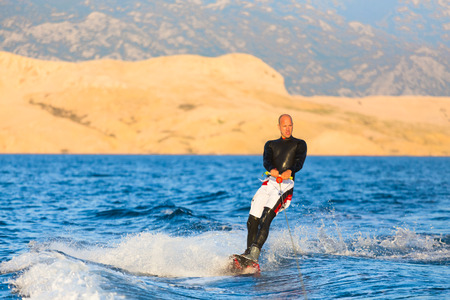 wakeboarding: Wakeboarder in wetsuit riding in sunset. Wakeboarding is a surface water sport which involves riding a wakeboard over the surface of a body of water. Stock Photo