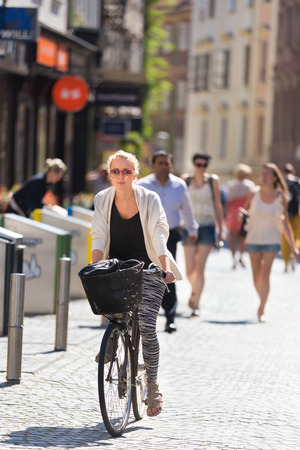 casualy: Casualy dressed lady riding bicycle trough medieval city center of Ljubljana, capital of Slovenia. Environmentally friendly and healthy way of urban transportation. Stock Photo