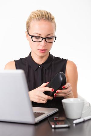diopter: Mujer de negocios que pone en sus gafas de dioptr�as negros para trabajar en la computadora port�til en la oficina.