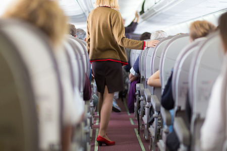 stewardess: Interior of airplane with passengers on seats and stewardess walking the aisle.