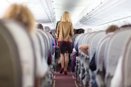 airline hostess: Interior of airplane with passengers on seats and stewardess walking the aisle.