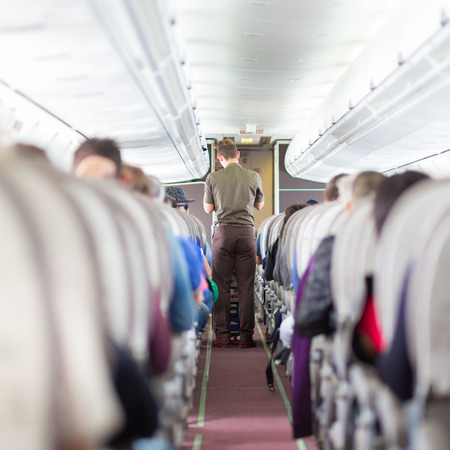steward: Interior of airplane with passengers on seats and steward walking the aisle.