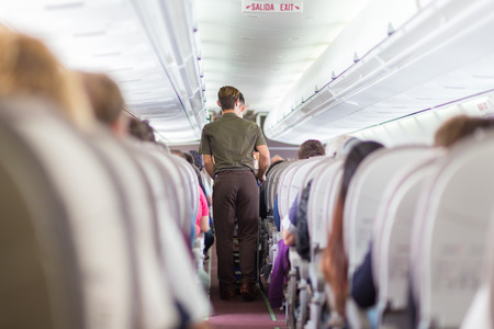 Interior of airplane with passengers on seats and steward walking the aisle. photo