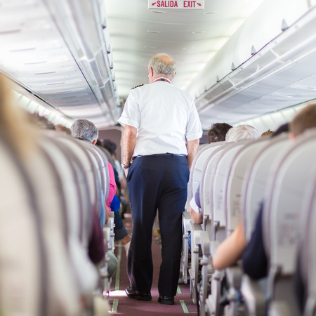 Interior of airplane with passengers on seats and pilot walking the aisle. photo