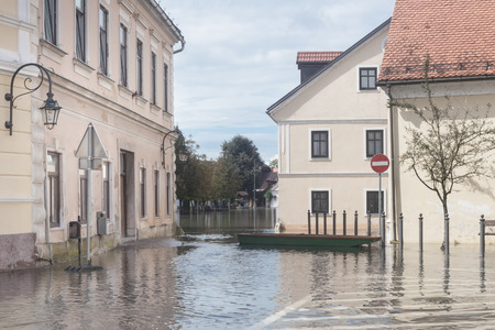 FLOODING: Rural village houses in floodwater. Road with the river overflown with the residents in their homes. River Krka floods and flooding the streets. Natural disaster in Kostanjevica, Slovenia. Stock Photo