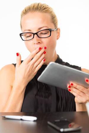 Business woman yawning while working on her tablet PC.