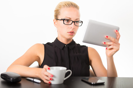 drowsiness: Business woman in office working on her tablet PC. White cup of coffee on her desk.