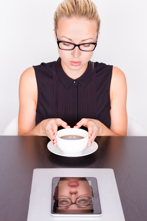 Business woman in contemporary office holding white cup of coffee in her hand. Her portrait reflects in tablet computer on working desk. photo