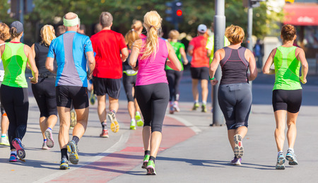 active woman: Group of active people running in the city. Healthy lifestyle. Weight Loss. Urban marathon run. Stock Photo