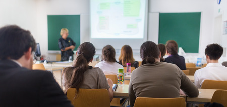 Teacher at university in front of a whiteboard screen. Students listening to lecture and making notes. photo