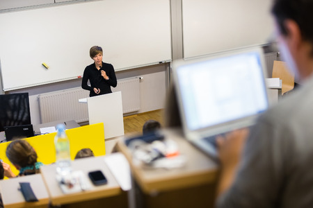 Speaker giving presentation in lecture hall at university. Participants listening to lecture and making notes. photo